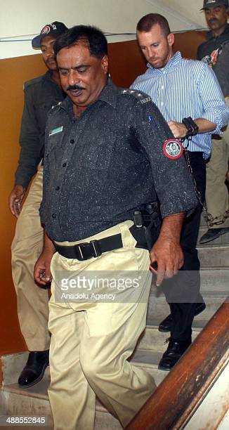 In this photograph taken on May 6 2014 Pakistani policemen escort an US FBI agent under arrest as they leave the local court in Karachi Pakistan An...