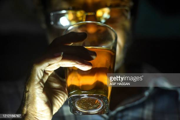 In this photograph taken on May 6 a man drinks a glass of alcohol in Karachi Drinking alcohol in Pakistan can be a complicated affair at the best of...