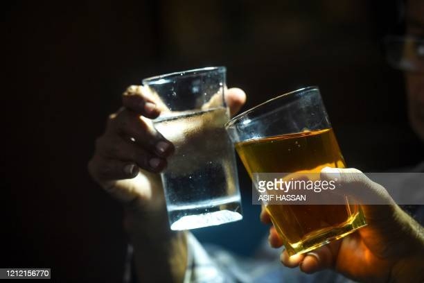 In this photograph taken on May 6 men toast with their glasses as they drink alcohol in Karachi. - Drinking alcohol in Pakistan can be a complicated...
