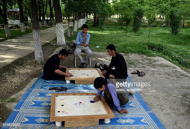 In this photograph taken on May 7 Afghan visitors play the board game 'carrom' as they relax at the BagheBabur Garden in Kabul Kabul's historic Baghe...