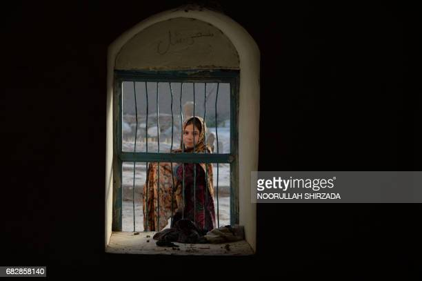 In this photograph taken on May 7 an Afghan girl looks through a window to a mentally ill patient chained to a wall at the Mia Ali Baba holy shrine...