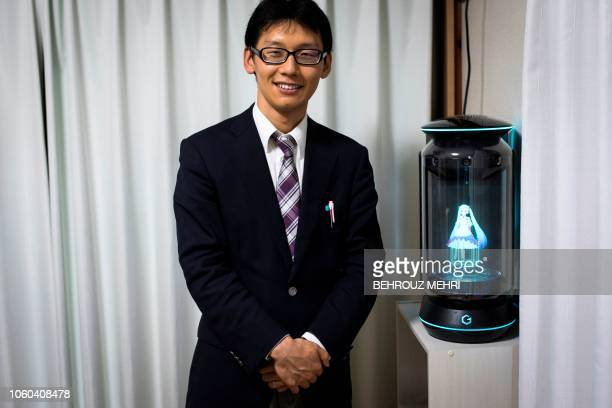 In this photograph taken on November 10 2018 Japanese Akihiko Kondo poses next to a hologram of Japanese virtual reality singer Hatsune Miku at his...