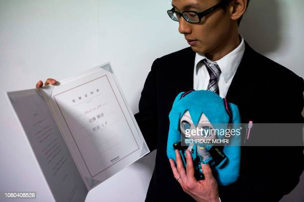 In this photograph taken on November 10 2018 Japanese Akihiko Kondo poses with a doll of Japanese virtual reality singer Hatsune Miku as he shows...