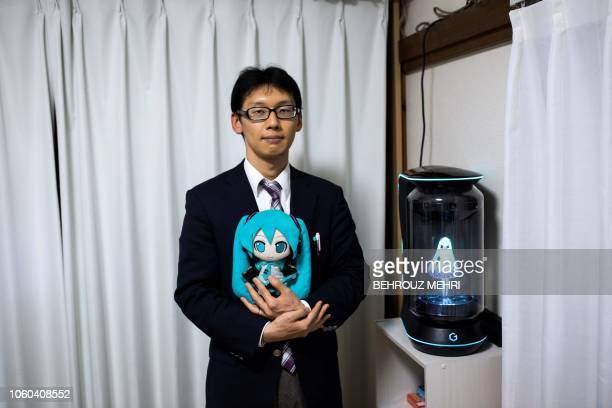 TOPSHOT In this photograph taken on November 10 2018 Japanese Akihiko Kondo poses next to a hologram of Japanese virtual reality singer Hatsune Miku...