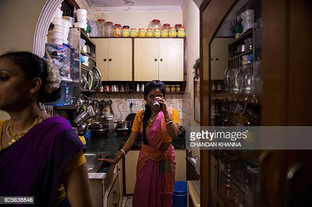 In this photograph taken on November 11 a dance student drinks water inside a kitchen during a dress rehearsal performance of the Bharatnatyam dance...
