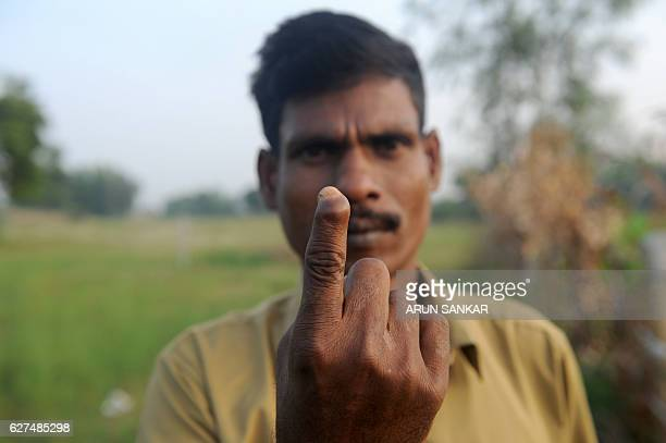 In this photograph taken on November 11 Indian snake catchers Kali of the Irula snakecatchers cooperative holds up his forefinger and displays a...
