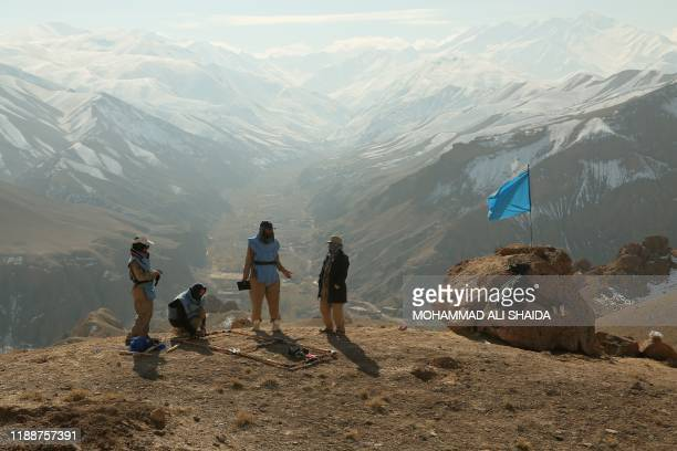 In this photograph taken on November 14 Afghan deminers working for the Danish Demining Group stand on a hill overlooking a valley during the...