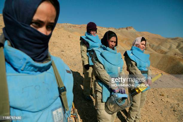 TOPSHOT In this photograph taken on November 14 Afghan deminers working for the Danish Demining Group look on during the scanning of a combat zone...