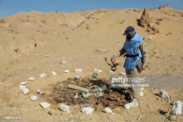 In this photograph taken on November 14 an Afghan deminer working for the Danish Demining Group holds parts of a mine during the scanning of a combat...