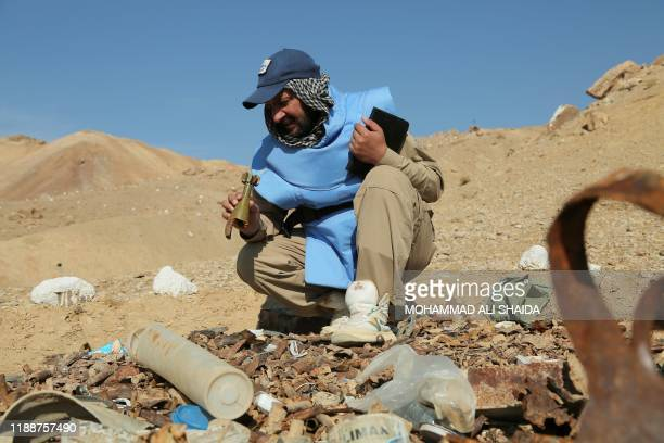 In this photograph taken on November 14 an Afghan deminer working for the Danish Demining Group holds a mortar bomb during the scanning of a combat...