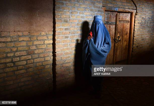 TOPSHOT In this photograph taken on November 16 a burqaclad Afghan woman walks in the old quarters of Herat / AFP / AREF KARIMI