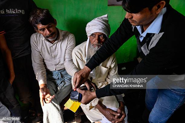 In this photograph taken on November 16 bank correspondent Mohammad Imran assists a villager his thumb print on a mobile banking machine in Basendua...