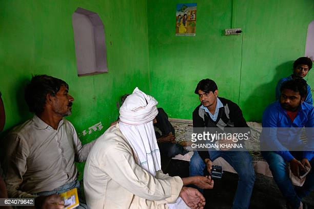 In this photograph taken on November 16 bank correspondent Mohammad Imran inputs bank details of villagers on a mobile banking machine in Basendua...