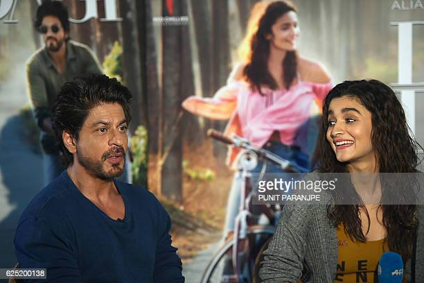 In this photograph taken on November 16 Bollywood actor Shah Rukh Khan speaks as actress Alia Bhatt looks on during an interview with AFP in Mumbai...