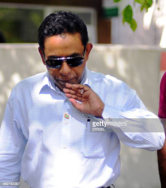 In this photograph taken on November 16 Maldivian presidential candidate Abdulla Yameen blows on his finger marked with ink after having cast his...