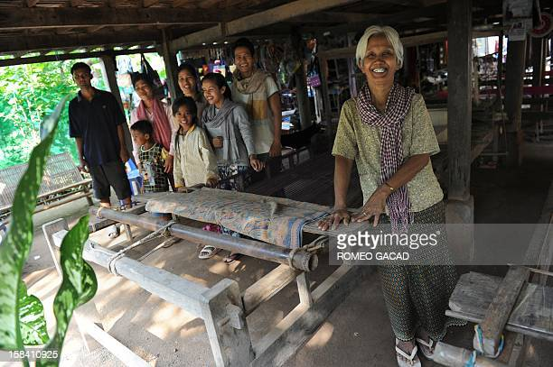 In this photograph taken on November 22 Cambodian grandmother Pres Noun poses with her children and grandchildren beside wooden looms at the family's...