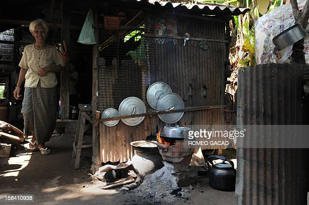 In this photograph taken on November 22 Cambodian grandmother Pres Nuon cooks rice water for soaking silk thread at her family's silk farm in Prek...