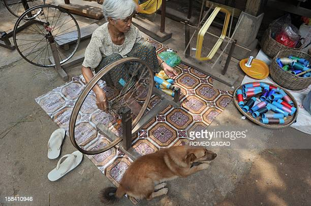 In this photograph taken on November 22 Cambodian grandmother Pres Noun spins gold coloured silk thread at her family's silk farm in Prek Bongkong...