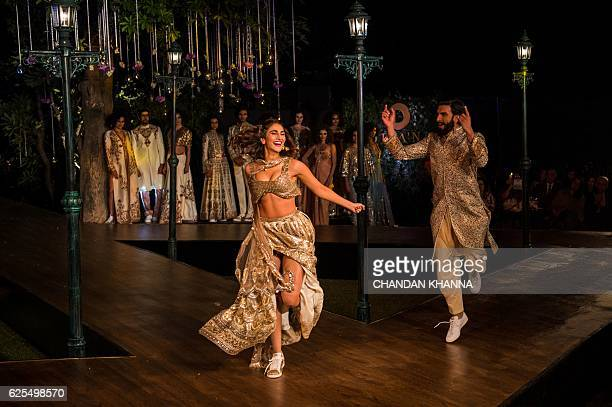 In this photograph taken on November 23 Bollywood actor Ranveer Singh dances with actress Vaani Kapoor during a promotional event for the forthcoming...