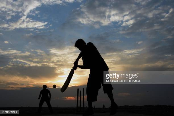 In this photograph taken on November 24 an Afghan man plays cricket on the outskirts of Jalalabad / AFP PHOTO / NOORULLAH SHIRZADA