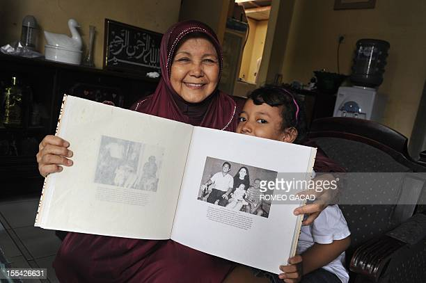 In this photograph taken on November 3 69 year old Indonesian grandmother Tien Soemitro and her grand daughter Tata display a family picture album...