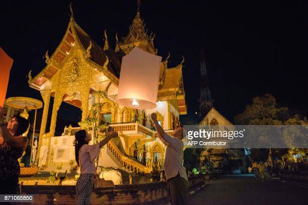 In this photograph taken on November 4 a man and a woman release a lit lantern at a local buddhist temple as they celebrate during the Loy Krathong...