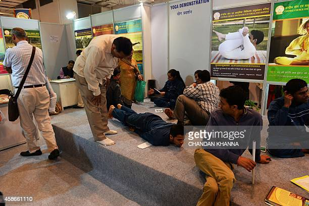 In this photograph taken on November 7 Indian visitors take advice from a yoga instructor at the sixth World Ayurveda Congress and Arogya Expo in New...