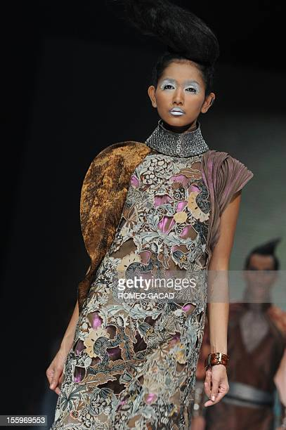 In this photograph taken on November 9 2012 a model presents a creation inspired by traditional Indonesian wayang figures by Indonesian designer Ghea...