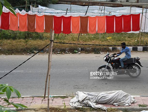 In this photograph taken on October 10 a motorcyclist passes a laundry worker sleeping under a line of washed clothes put out to dry in the early...