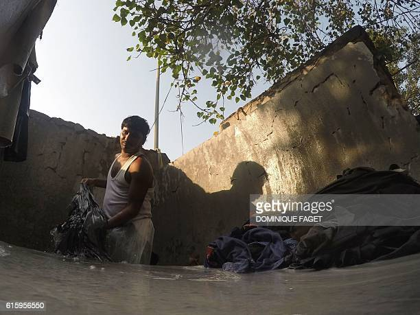 In this photograph taken on October 12 laundry worker Dharam Nath stands in a stone bath as he beats items of clothing to clean and rinse then at an...