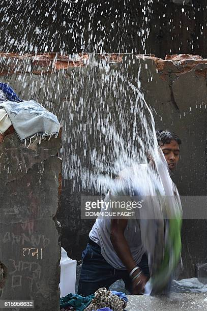 In this photograph taken on October 12 laundry worker Rajesh stands in a stone bath as he beats items of clothing to clean and rinse then at an...
