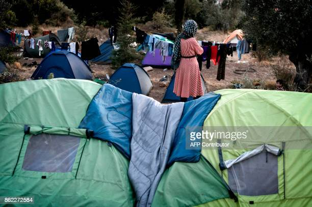 In this photograph taken on October 13 a woman stands among the tents of recently arrived refugees in the woods on the Greek island of Samos Nearly...