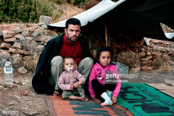 In this photograph taken on October 13 refugees pose as they sit by their shelter in woods on the Greek island of Samos Nearly 300 Syrians Iraqis...
