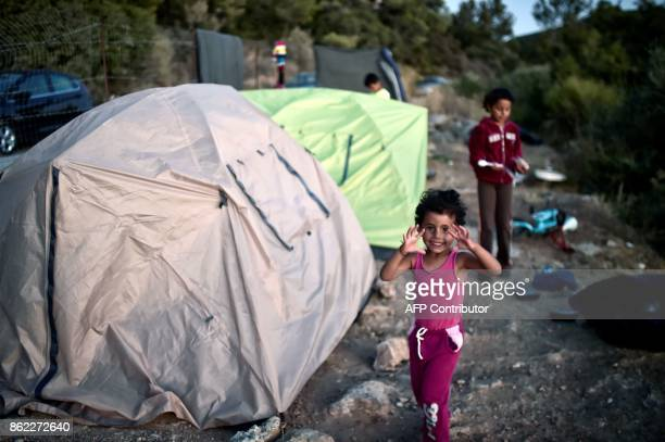 In this photograph taken on October 13 young recently arrived refugees pose by their shelter in woods on the Greek island of Samos Nearly 300 Syrians...