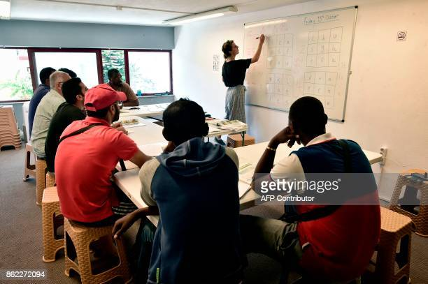 In this photograph taken on October 13 young refugees attend an English language course in the 'Alpha' refugee support centre on the Greek island of...