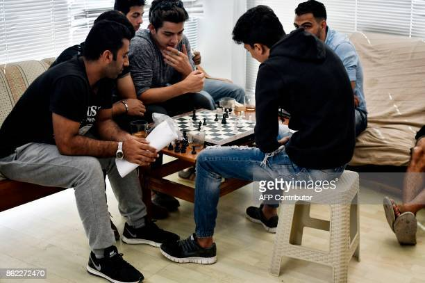 In this photograph taken on October 13 young refugees play chess in the 'Alpha' refugee support centre on the Greek island of Samos Nearly 300...
