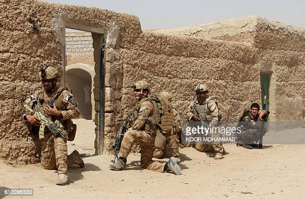 In this photograph taken on October 2 Afghan National Army commandos take position during a military operation in Helmand province. / AFP / NOOR...