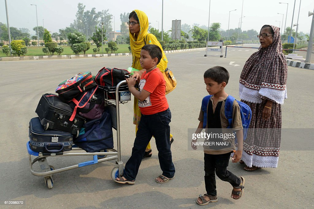 In this photograph taken on October 2 Pakistan travellers Quratulain and Kaneza Khatoon and unidentified children leave India for Pakistan on foot at.