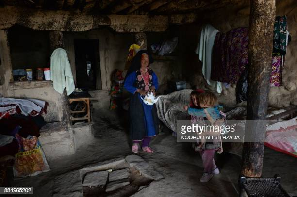 TOPSHOT In this photograph taken on October 21 2017 Afghan widow Janat Bibi holds a teapot walks inside her mud house in the remote village of Shemol...