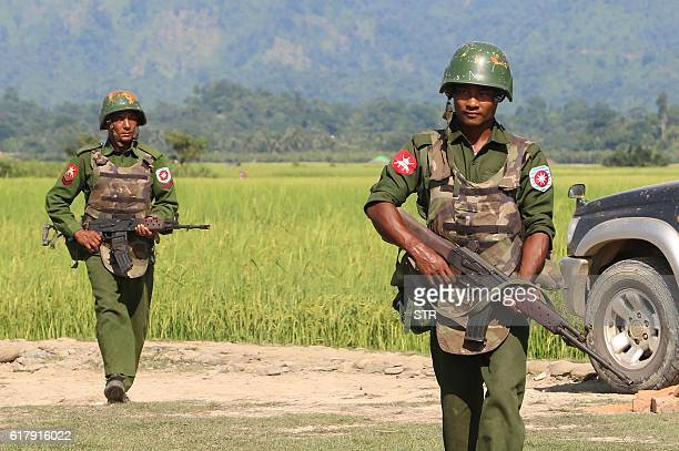 In this photograph taken on October 21 armed Myanmar army soldiers patrol a village in Maungdaw located in Rakhine State as security operation...