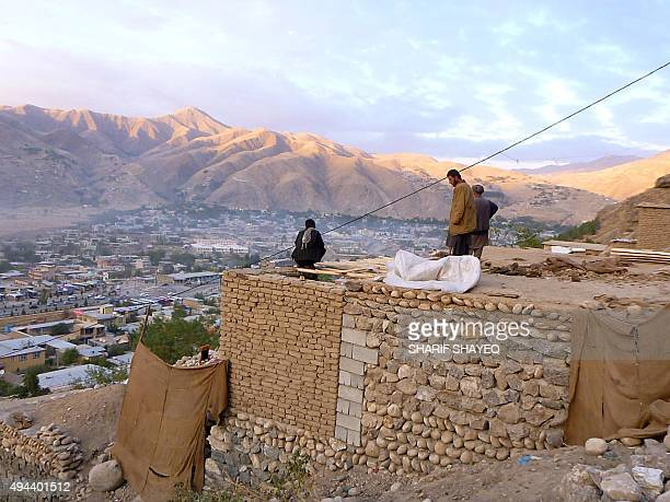 In this photograph taken on October 26 Afghan householders gather on the roof of a house Faizabad in Badakhshan Province after a powerful earthquake...