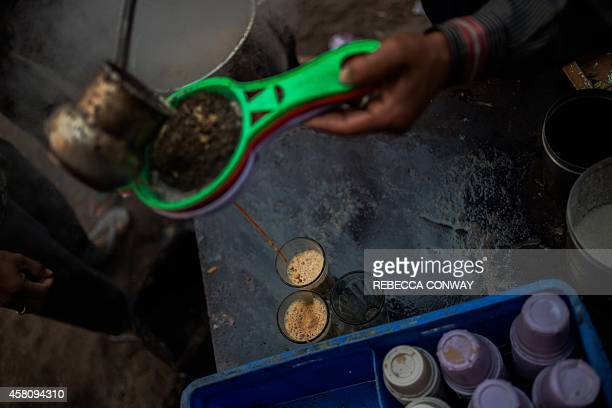 In this photograph taken on October 26 an Indian tea stall owner pours masala chai or spiced tea made with cardamom and ginger for customers in the...