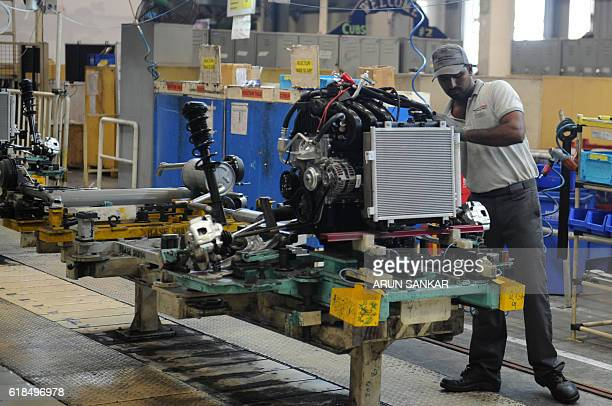 In this photograph taken on October 26 Indian workers labour on assembly lines of components for Datsun Go and Renault Kwid vehicles at Renault...