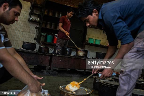 In this photograph taken on October 29 Indian cook Salman makes chicken korma as Zurick Khan and Monu Khan pack chicken biryani at Babu Shahi...