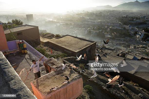 In this photograph taken on October 3 Ahmad an Afghan man who lives in the hill side neighbourhood of Jamal Mina and makes a living by making and...