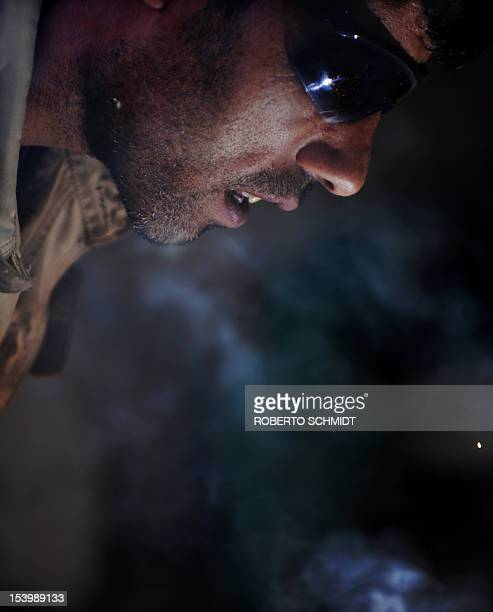 In this photograph taken on October 3 Ahmad an Afghan man who lives in the hill side neighbourhood of Jamal Mina in Kabul and makes a living by...