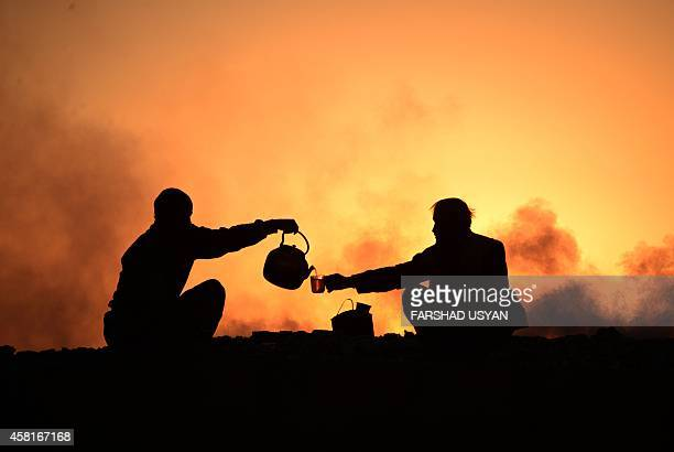 In this photograph taken on October 30 Afghan labourers drink tea after work at a chalk factory as the sun sets on the outskirts of Mazarisharif...