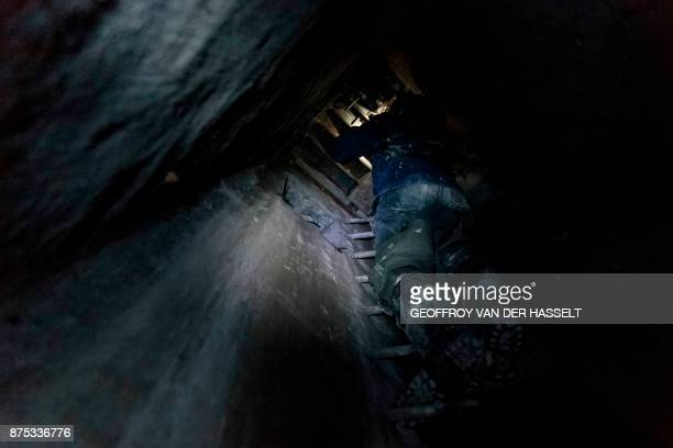 In this photograph taken on October 31 a person opens a trapdoor in a technical gallery to exit the banned catacombs of Paris The underground...