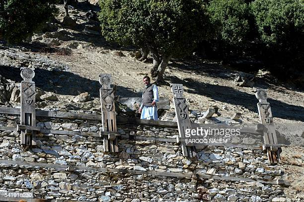 In this photograph taken on October 31 Kalash activist Luke Rehmat speaks during an interview with AFP infront of altars at a Kalash heritage site in...