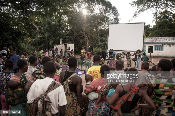 TOPSHOT In this photograph taken on October 31 residents of a village of the Mbyaka people gather as they wait for a film screening at a mobile...